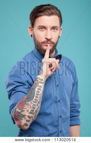 Attractive bearded man is asking for silence
