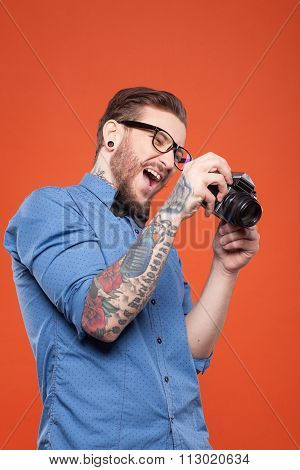 Attractive young bearded hipster is making photos