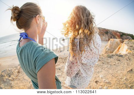 Two young ladies walking on the rocky land towards the cliff's edge and ocean. Praia do Tonel beach, Portugal