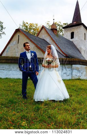the bride and groom in front of a historical church.