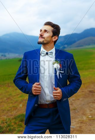 young handsome groom in blue wedding suit in mountain landscape.