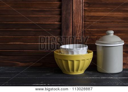 Rustic Kitchen Still Life. Vintage Ceramic Bowl And Enameled Jar On Dark Wooden Table
