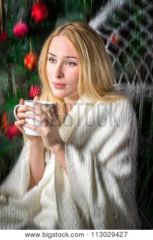 Young Woman Sipping Tea Or Coffee From A Cup While Sitting On Armchair Wrapped In Warm Cozy Plaid Ne