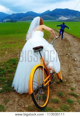 bride on orange retro bike is chasing after a groom in blue wedding suit with a beer bottle. wedding