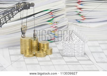 House And Pile Of Gold Coins With Hook Of Crane