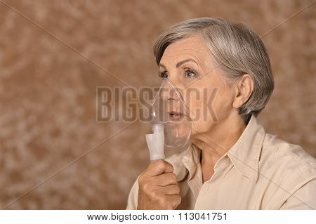 Senior woman making inhalation