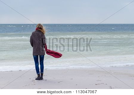 Lone sad beautiful girl walking along the shore of the frozen sea on a cold day, rubella, chicken wi