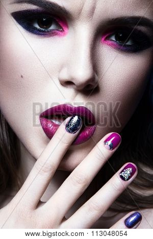 Beautiful girl with bright creative fashion makeup and colorful nail polish. Art beauty design.