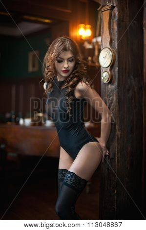 Young beautiful brunette woman in black tight fit corset posing sensual in vintage scenery