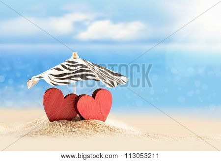 Two Hearts Under Umbrella On The Beach. Valentines Day.