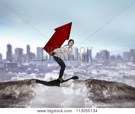 Woman Carry Heavy Red Arrow Shape Above Her Colleague Across The Mountain