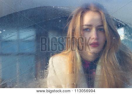 sad beautiful seksalnaya Pretty sad lonely girl behind wet glass with big sad eyes in a coat