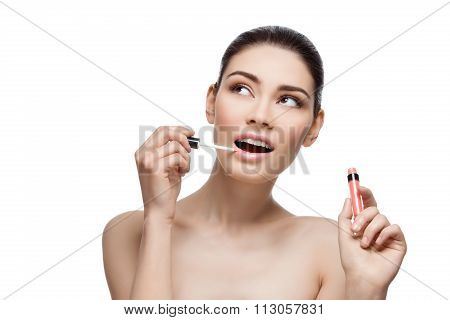 Beautiful girl applying lipgloss