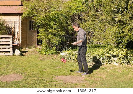 Man Plays Diabolo In His Garden At Summer
