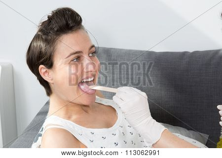 Nurse Putting Tongue Depressor Into Caucasian Pregnant Woman's Mouth.