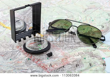 Compass and pilot sunglasses on a hiking map of the Berchtesgaden Alps