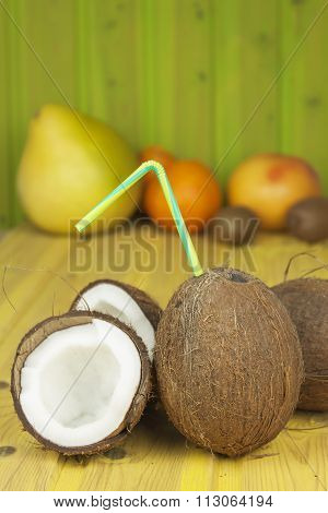 Cracked coconut on yellow wooden table. Preparing coconut refreshing drink. Tropical drink.