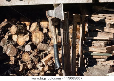 stack of untidy firewood with ax