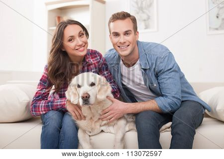 Pretty loving couple and puppy at home
