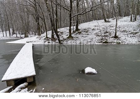 A Narrow Footbridge To The Newly Frozen Pond.