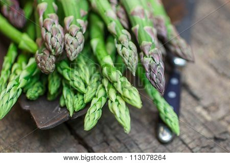 Fresh green asparagus on old wooden table. Shallow depth of field