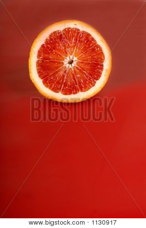 Juicy Half Of A Blood Orange On A Red Background