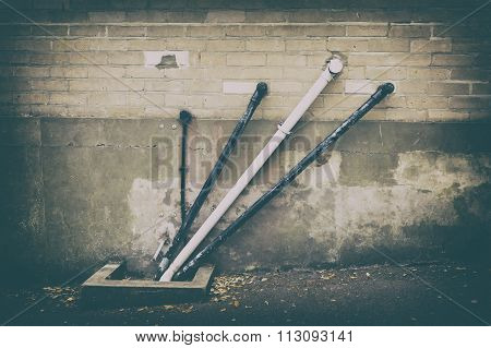 A Photo Of Black And White Angular Water Pipes On A Beige Brickwork Wall With A Strong Vintage Filte