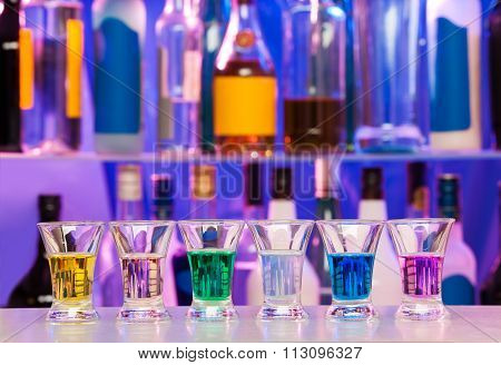 Big row of shots glasses with color drinks