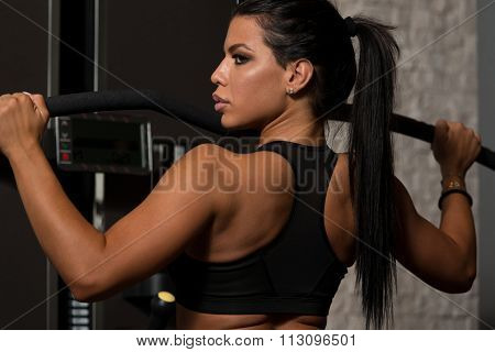 Latino Woman Doing Exercise For Back On Machine