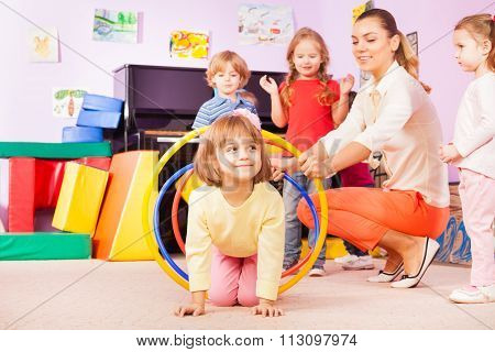 Girl crawl in plastic hoop, kindergarten group