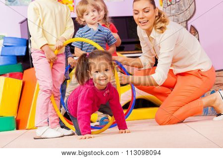 Kids with girl and teacher play active game