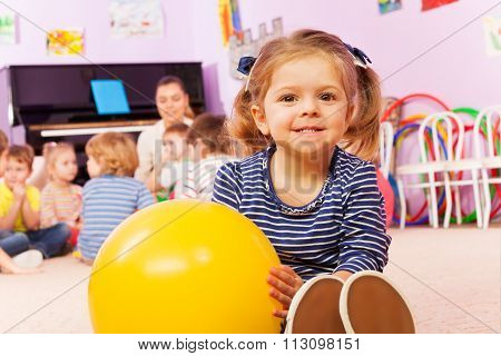 Little girl with ball sit in developmental class