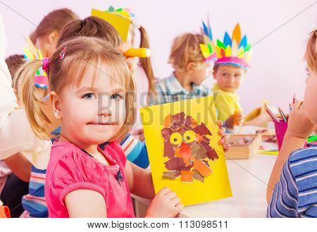 Little girls in craft class show handmade postcard with paper glued to cardboard and mates boys and girls on background
