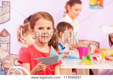 Girl makes origami in kindergarten class