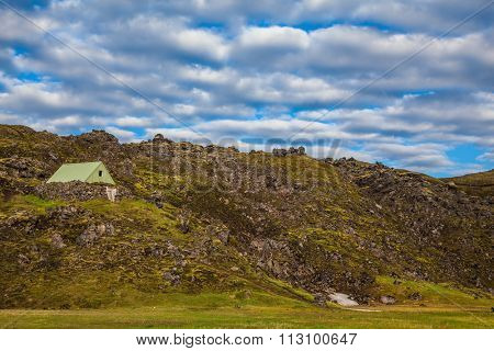 Summer trip to Iceland. The green lawn in the Valley National Park Landmannalaugar. Tourist house lava slope