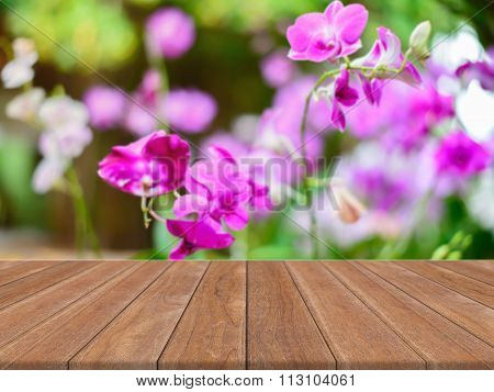 Perspective brown wood over blur flower in forest - can be used for display or montage your products