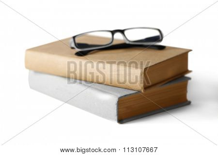 Hard covered books and eyeglasses on it isolated on white background