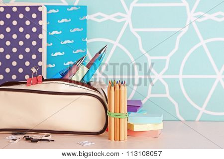 Pencil case with various stationery on wooden table, close up