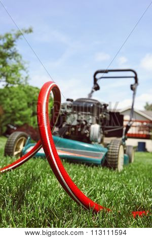 Red garden hose outdoors laying in grass in front of lawnmower.
