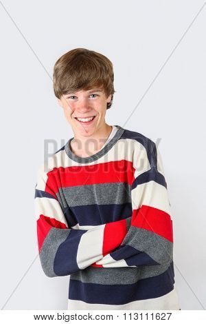 Smiling teen with acne, on a gray background