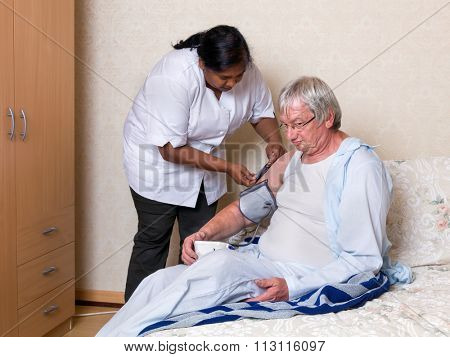 Friendly nurse checking blood pressure of an elderly man in a nursing home