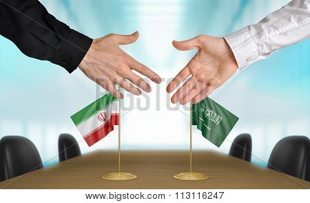 Iran and Saudi Arabia diplomats shaking hands to agree deal