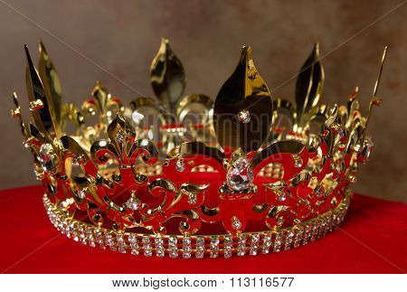 Medieval golden king's crown on red velvet pillow