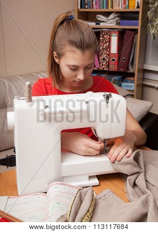 Girl Sews On The Sewing Machine