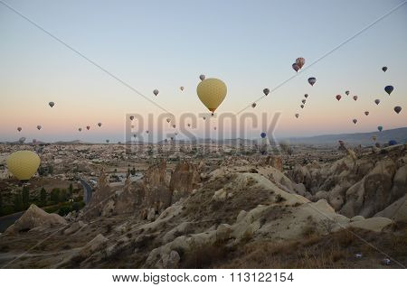 Hot air balloons over hilly landscape at Cappadocia