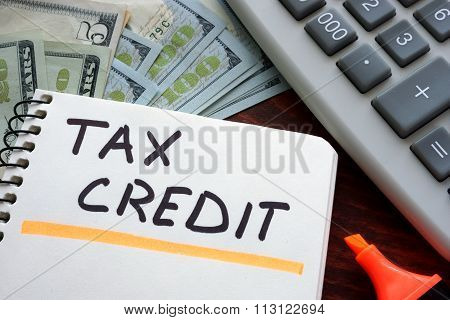 Notebook with  tax credit sign on a table.