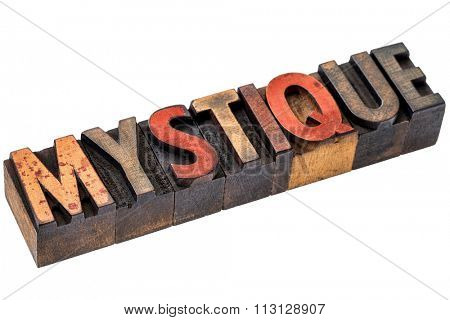 mystique word abstract  - an isolated banner in vintage letterpress wood type stained by color inks