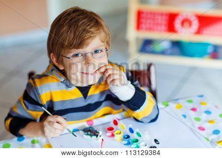 Little kid boy drawing with colorful watercolors indoors