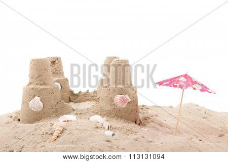 Beach with sandcastle, shells and parasol on white background
