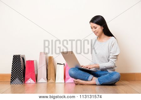 Asian woman use of the notebook computer for online shopping